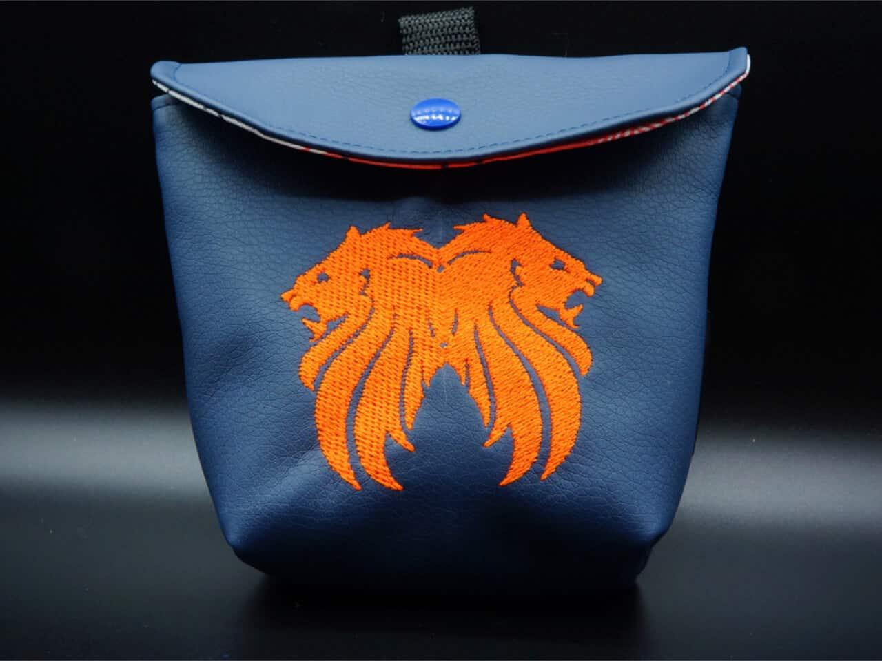 Futtersack in blauem Kunstleder mit orangen Doppellöwen bestickt